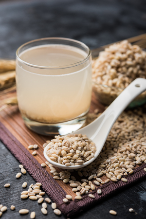 Barley water in glass with raw and cooked pearl barley wheat/seeds. selective focus