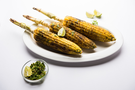Delicious Indian street corn cob also called Bhutta, flavoured with spicy chilli, butter etc. Selective focus