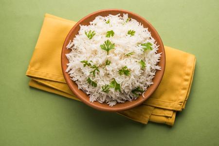 Ryż Basmati z kolendrą lub kolendrą, podawany w misce ceramicznej lub terakotowej. To popularny przepis indyjski LUB chiński. Selektywna ostrość