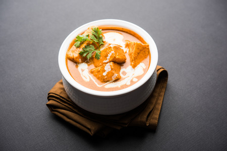 Paneer Butter Masala also known as Panir  makhani or makhanwala. served in a ceramic or terracotta bowl with fresh cream and coriander. Isolated over colourful moody background. selective focus Фото со стока