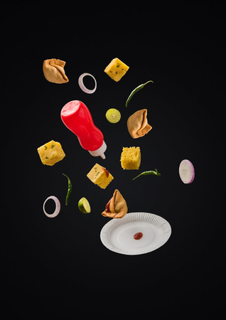 Samosa and Khaman Dhokla flying with ketchup bottle, green chilli, lemon and plate over plain background
