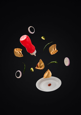 Tasty Samosa Snacks flying with ketchup bottle, green chilli, onion slices and plate over plain background