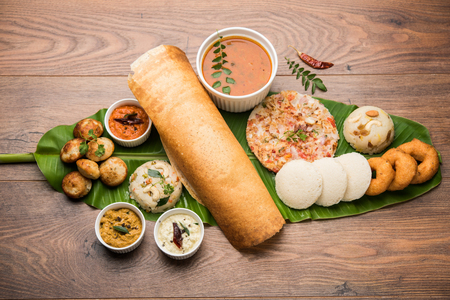 Group of South Indian food like Masala Dosa, Uttapam, Idli/idly, Wada/vada, sambar, appam, semolina halwa, upma served over banana leaf with colourful chutneys, selective focus Banco de Imagens