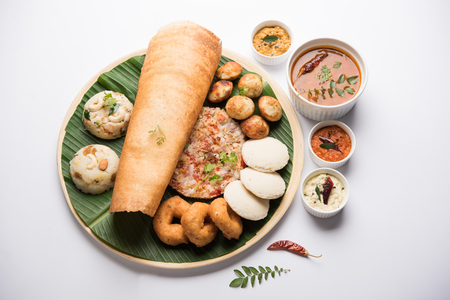 Group of South Indian food like Masala Dosa, Uttapam, Idli/idly, Wada/vada, sambar, appam, semolina halwa, upma served over banana leaf with colourful chutneys, selective focus 스톡 콘텐츠