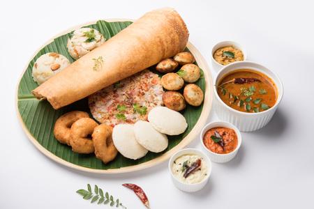 Group of South Indian food like Masala Dosa, Uttapam, Idli/idly, Wada/vada, sambar, appam, semolina halwa, upma served over banana leaf with colourful chutneys, selective focus Stockfoto