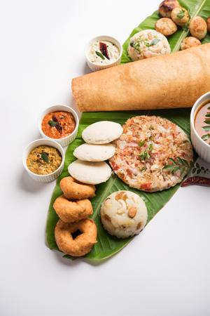 Group of South Indian food like Masala Dosa, Uttapam, Idli/idly, Wada/vada, sambar, appam, semolina halwa, upma served over banana leaf with colourful chutneys, selective focus Stock Photo