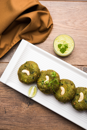 Hara bhara Kabab or Kebab is Indian vegetarian snack recipe served with green mint chutney over moody background. selective focus