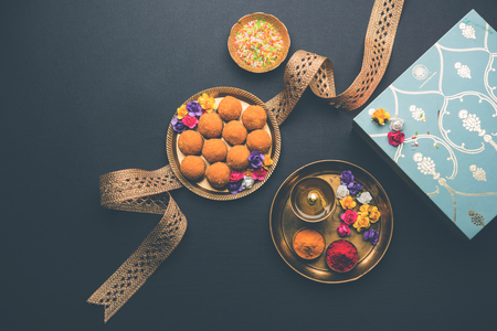 Raksha bandhan Festival : conceptual Rakhi made using plate full of Bundi Laddu sweet with band and Pooja Thali. A traditional Indian wrist band which is a symbol of love between Brothers and Sisters Stock Photo