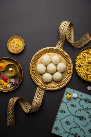 Raksha bandhan Festival : conceptual Rakhi made using plate full of Rasgulla sweet with band. A traditional Indian wrist band which is a symbol of love between Brothers and Sisters Stock Photo