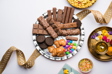 Raksha bandhan Festival greetings: conceptual Rakhi made using a plate full chocolates and biscuits with fancy band and pooja Thali. selective focus