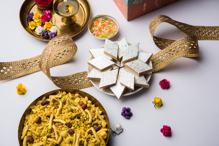 Raksha bandhan Festival greetings: conceptual Rakhi made using a plate full of Kaju Katli BarfiBurfi and fancy band and pooja Thali. selective focus Stock Photo