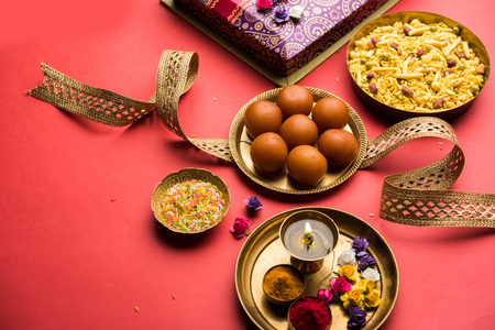 Raksha bandhan Festival : conceptual Rakhi made using plate full of Gulab Jamun sweet with band and Pooja Thali. A traditional Indian wrist band which is a symbol of love between Brothers and Sisters Stock Photo