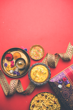 Raksha bandhan Festival : conceptual Rakhi made using Shrikhand in a bowl with band and Pooja Thali. A traditional Indian wrist band which is a symbol of love between Brothers and Sisters Stock Photo
