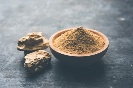 FullerS Earth Clay OR Multani mitti in a bowl along with raw stones and mortar Фото со стока