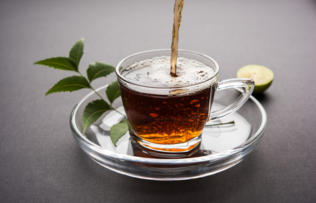 pouring Neem tea in transparent glass cup with saucer over white background. Popular Ayurvedic medicine from India