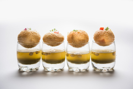 Pani Puri is an indian road side chat item - 4 stuffed puris kept over small glasses filled with mint water Banque d'images - 106925844