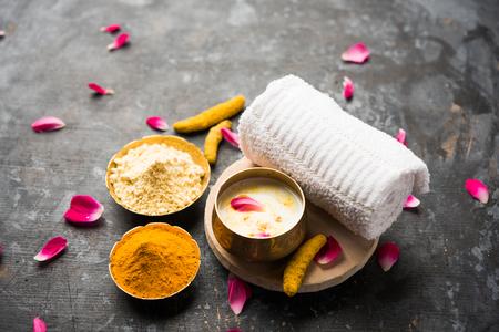 Ayurvedic face packmask using Gram Flourbesan, Haldi & milk ubtan placed in brass bowls with rose petals, scrub  and white napkin. selective focus Stock fotó