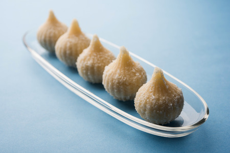 Sweet Modak made using coconut, khoya and sugar. Popular Maharashtrian recipe offered to lord Ganesha in Ganesh Festival. Served in a plate. Selective focus Stock Photo