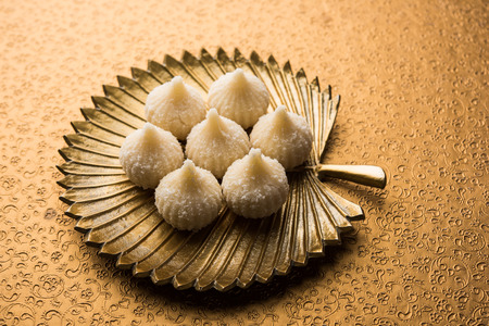 Sweet Modak made using coconut, khoya and sugar. Popular Maharashtrian recipe offered to lord Ganesha in Ganesh Festival. Served in a plate. Selective focus 版權商用圖片