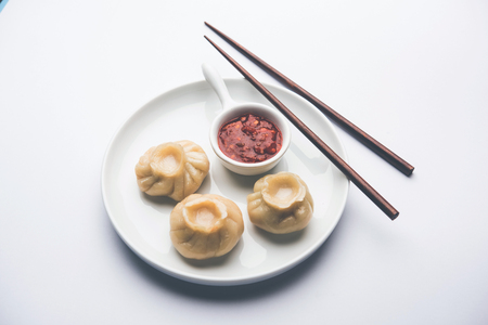 Dumpling momos food from Nepal or Ladakh served with red chilli chutney over moody background. Selective focus