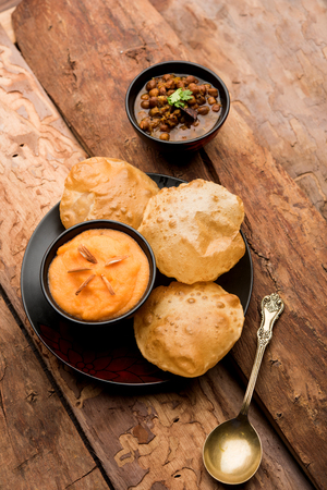 Suji/Sooji Halwa Puri or Shira Poori with black chana masala breakfast, served in a plate and bowl. selective focus
