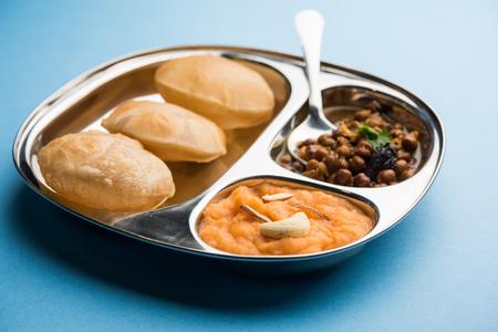 SujiSooji Halwa Puri or Shira Poori with black chana masala breakfast, served in a plate and bowl. selective focus