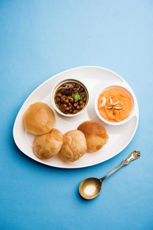 Suji/Sooji Halwa Puri or Shira Poori with black chana masala breakfast, served in a plate and bowl. selective focus