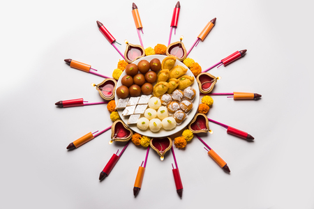 Rangoli or design made using Diyaoil lamp with Indian snackssweet and firecrackers