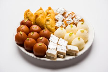 Zu den indischen Süßigkeiten auf einem Teller gehören Gulab Jamun, Rasgulla, Kaju Katli, Morichoor / Bundi Laddu, Gujiya oder Karanji für die Diwali-Feier Standard-Bild