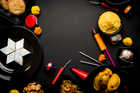 Diwali Süßigkeiten und Snacks in einer Gruppe mit Diya oder Öllampe, Blumen und Feuerwerkskörpern oder Patakhe über launischen Hintergrund angeordnet