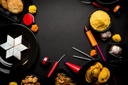 Dolci e snack Diwali disposti in gruppo con Diya o lampada a olio, fiori e Fire Crackers o Patakhe su sfondo lunatico
