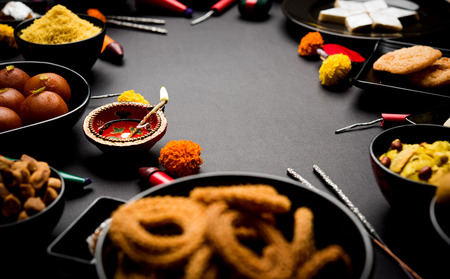 Diwali sweets and snacks arranged in a group with Diya or oil lamp, flowers and Fire Crackers or Patakhe over moody background