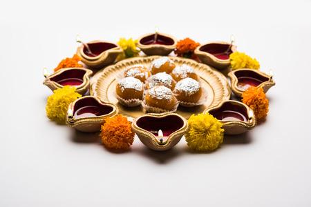 Diwali Rangoli using Diya, flowers and Motichoor Laddu or Boondi Laddoo arranged over white background, selective focus Stock Photo