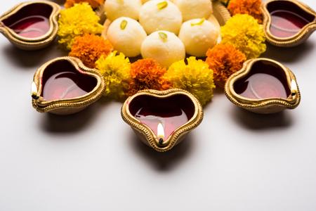 Diwali Rangoli using Diya/oil lamp, flowers and Rasgulla/rosogulla arranged over white background, selective focus