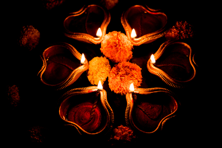 Beautiful diwali diyas at night with flowers, lighting series and gifts, moody background Stock Photo