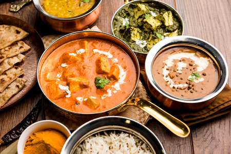 Indian Lunch / Dinner main course food in group includes Paneer Butter Masala, Dal Makhani, Palak Paneer, Roti, Rice etc, Selective focus Stock Photo