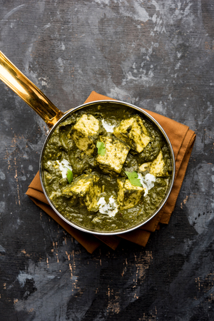Palak Paneer Curry ze szpinaku i twarogu podawane w misce lub patelni z roti lub ryżem