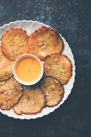 Malpua sweet - Traditional Indian dessert or pancake for festivals, served in plate with rabrirabdi . selective focus