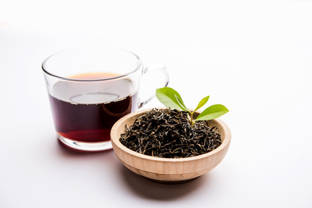 Black Tea Powder or dry dust with or without green leaf and served hot chai in a cup Foto de archivo