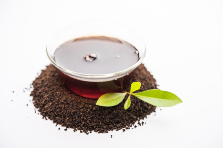 Black Tea Powder or dry dust with or without green leaf and served hot chai in a cup Banque d'images