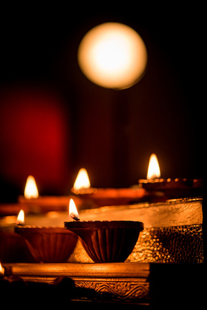 Diwali diya or lighting in the night with gifts, flowers over moody background. Selective focus Banque d'images