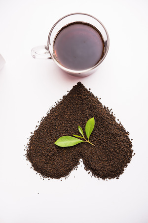 Black Tea Powder or dry dust with or without green leaf and served hot chai in a cup Stock Photo