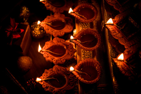 Diwali diya or lighting in the night with gifts, flowers over moody background. Selective focus Banco de Imagens