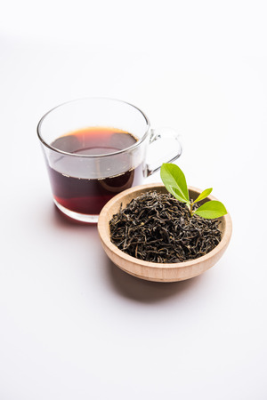 Black Tea Powder or dry dust with or without green leaf and served hot chai in a cup 写真素材