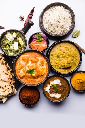 Indisches Mittag- / Abendessen Hauptgericht in der Gruppe beinhaltet Paneer Butter Masala, Dal Makhani, Palak Paneer, Roti, Reis usw., Selektiver Fokus Standard-Bild
