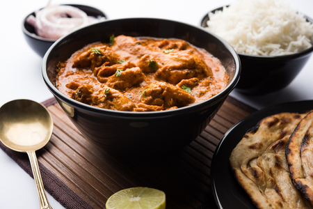 Murgh Makhani / Poulet au beurre tikka masala servi avec roti / Paratha et riz nature accompagné d'une salade d'oignons. mise au point sélective