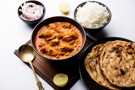 Murgh Makhani / Butter Chicken Tikka Masala serviert mit Roti / Paratha und einfachem Reis zusammen mit Zwiebelsalat. selektiver Fokus