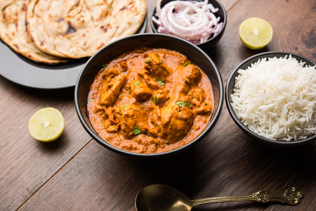 Murgh Makhani  Butter chicken tikka masala served with roti  Paratha and plain rice along with onion salad. selective focus