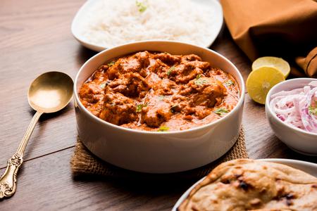 Murgh Makhani / Pollo tikka masala con mantequilla servido con roti / Paratha y arroz simple junto con ensalada de cebolla. enfoque selectivo