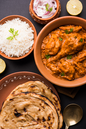 Murgh Makhani / Butter chicken tikka masala served with roti / Paratha and plain rice along with onion salad. selective focus Фото со стока
